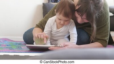 Young Mother using Tablet with her Baby Daughter. 4K...