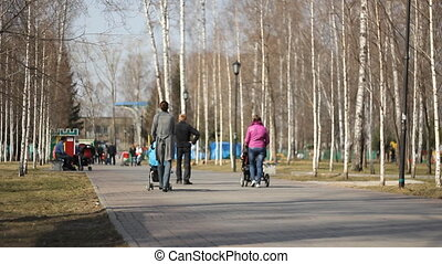 Young mother walking in a city park