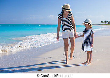 Young mother walking with her daughter along the caribbean beach