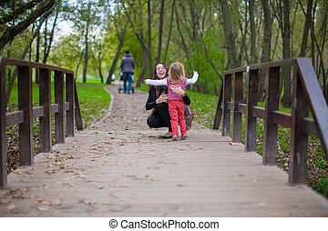 Young mother walking with her little daughter in autumn park