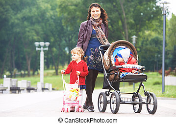 Young mother walking with pram and kids in park