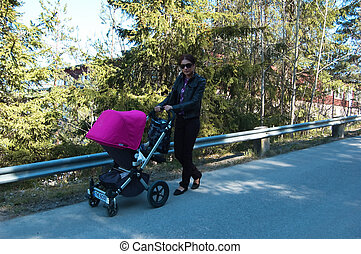 Young mother walking with pram