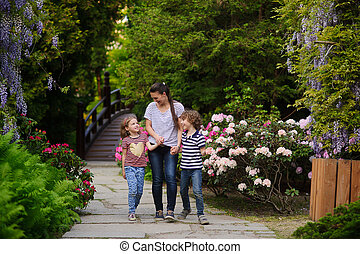 Young mother walks in the park with two children