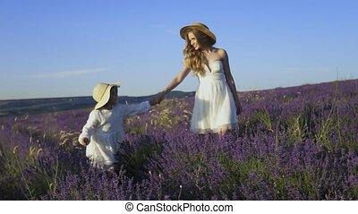 Young mother walks with a baby over a lavender field in slow motion