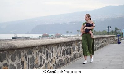 Young mother walks with her son baby on the waterfront near the ocean on the ancient square of Europe looks at the waves and smiles