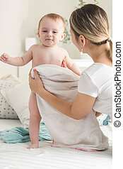 Young mother wiping her baby boy with towel on bed