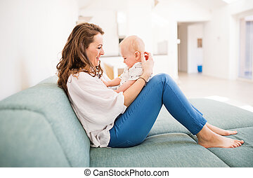 Young mother with a baby boy at home, sitting on the sofa.