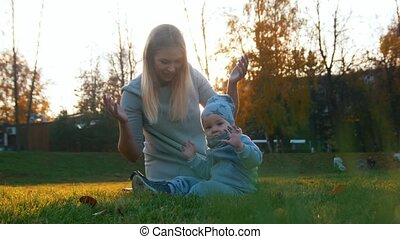Young mother with a baby playing in the autumn park on sunset. Looking in the camera