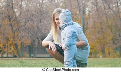 Young mother with a baby walking in the autumn park.