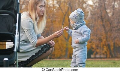 Young mother with a baby walking in the autumn park. Mother takes away garbage from a child's hands