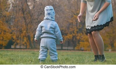 Young mother with a baby walking in the autumn park. Mother tickles her baby