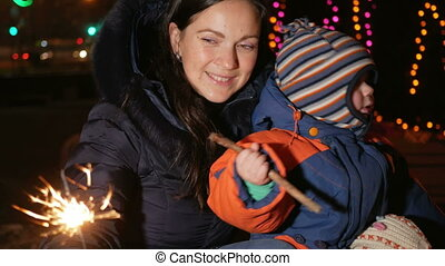 Young mother with a child celebrate the new year on the street with a sparkler. Hugging and smiling at the camera. Against the background is decorated Christmas tree