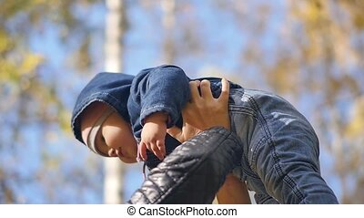 Young mother with a small child in the autumn park. A beautiful woman is spinning with her little daughter against the background of yellowing foliage on an autumn sunny day. Slow motion