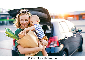 Young mother with baby boy in front of a supermarket.