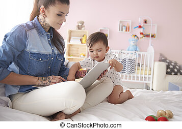 Young mother with baby boy using laptop at home