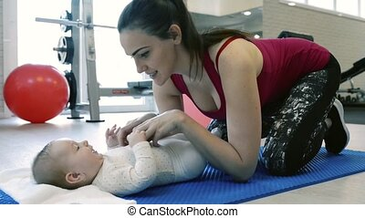 Young mother with baby daughter in gym resting on mat.