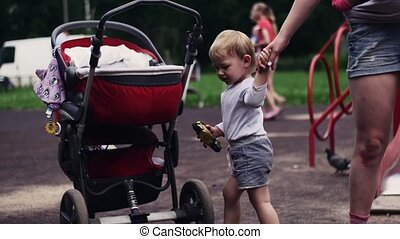 Young mother with baby in sling put crying son in baby carriage on playground.