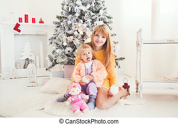 young mother with baby near Christmas tree