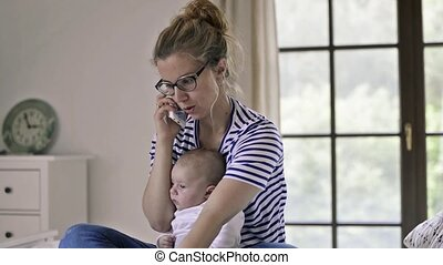 Young mother with baby son, sitting on bed, smartphone