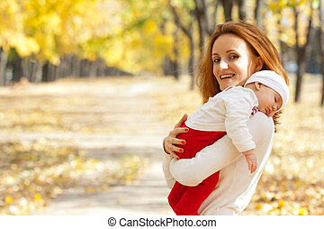 Young mother with child walking in autumn park