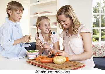 Young mother with children peeling vegetables in kitchen