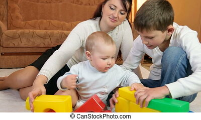 young mother with children playing colored blocks on the floor of living room
