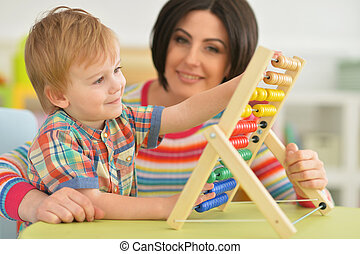 Young mother with cute little son learning