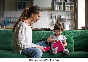 Young mother with daughter looking in opened box