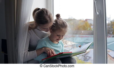 Young mother with daughter reading a book near the window