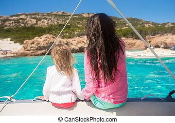 Young mother with her adorable daughter resting on a big boat