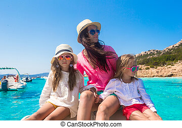 Young mother with her adorable daughters resting on a big boat