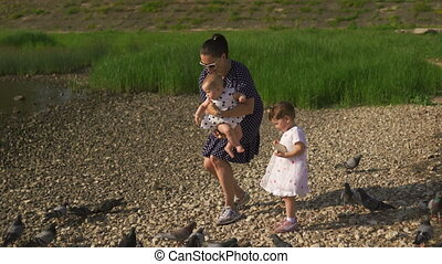 Young mother with her baby girl daughters feeding swan and...