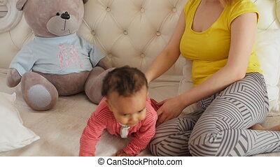 young mother with her baby having fun at home