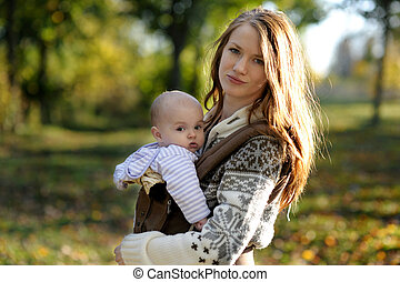 Young mother with her baby in a carrier