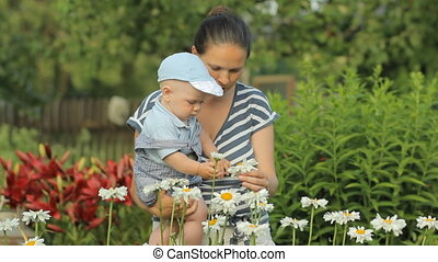Young mother with her beautiful boy touching flowers near his home. The son looks at the plants attentively