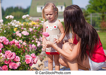 Young mother with her beautiful daughter sniffing flowers in the garden