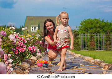 Young mother with her cute daughter have fun in the garden