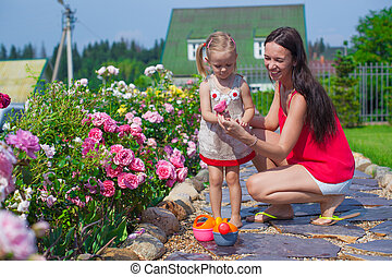 Young mother with her cute daughter near flowers in the garden