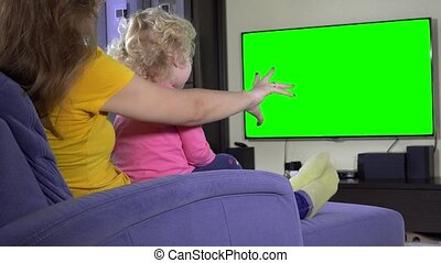 Young mother with her daughter girl relax on sofa and watch tv. Green screen