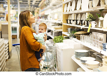 Young mother with her little baby girl at the supermarket