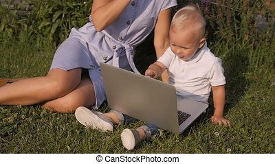 Young Mother With Her Little Cute Son Sitting On Grass And Using Laptop.