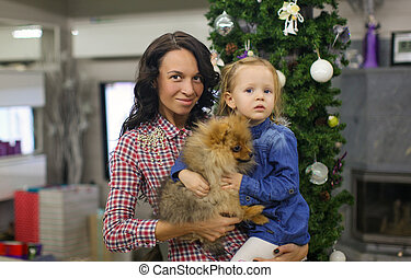 Young mother with her little daughter and cute dog on the eve of New Year at Christmas tree