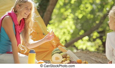 Young mother with her little daughter at picnic in the forest