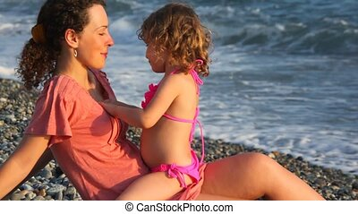 young mother with her little daughter playing in pebble beach near sea