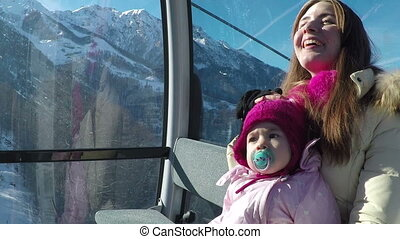 young mother with her little daughter riding on cableway in the mountains on a sunny day in winter. Slow motion
