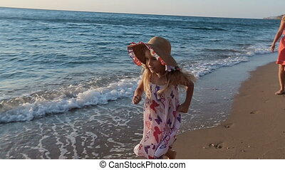 Young mother with her little daughter running to father with baby in his arms along the beach in slow motion