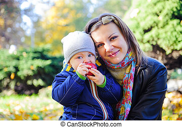 Young mother with her little son in autumn park