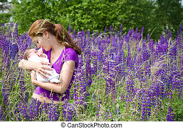 Young mother with her newborn baby in purple lupines field
