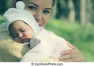 young mother with her newborn baby outdoor