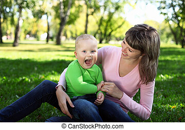 Young mother with her son in summer park